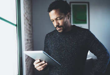 Selective focus.Pensive bearded African man using tablet while standing near the window in his modern apartment.Concept of young business people working at home.Blurred background.