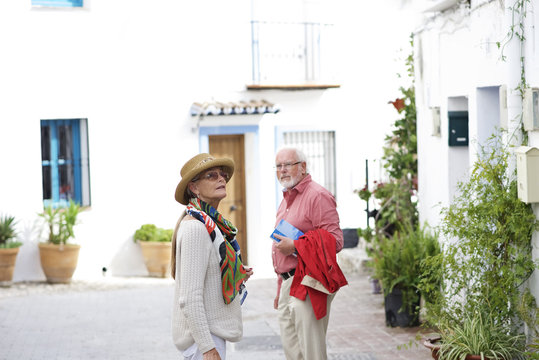 Senior couple exploring a typical Spanish town whilst on holiday