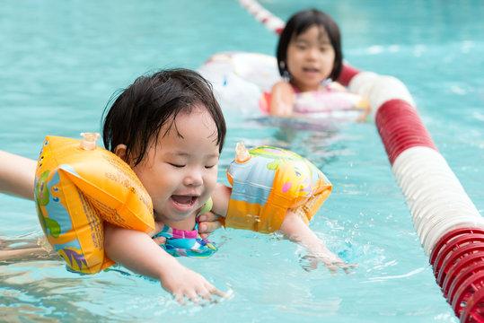 Little Asian toddler swimming