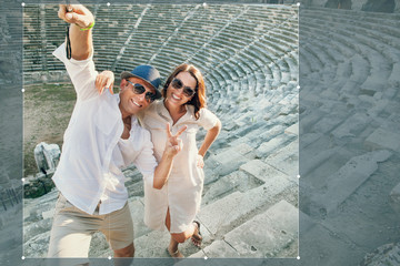 Funny couple take a selfie photo in antique amphitheatre in Side