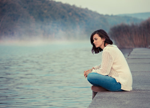 Lonely woman. Young woman sitting by lake in the early morning.