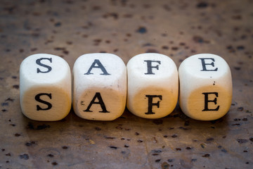 Safe text on wooden cubes on a brown cork background
