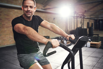 Young smiling man training on cycling machine