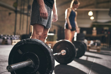 Man and woman going to lift barbells