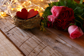 bouquet of roses and couple of red hearts in the nest