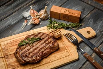 Pork steak on wooden Board with herbs, garlic and black pepper