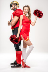 Football player standing with cheerleader