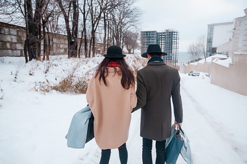 Young hipster beautiful couple in black hats in the winter forest,love,winter vacation in mountains,jeans,warm coat,traveling,hiking,winter walk in love,man in a green coat.girl in a beige coat