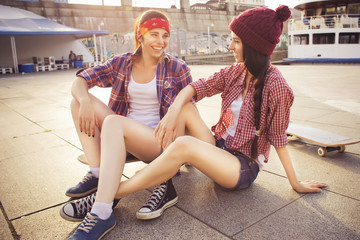 Two Brunette teenage girls friends in hipster outfit (jeans shorts, keds, plaid shirt, hat) with a skateboard at the park outdoors.