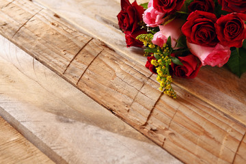 Beautiful bouquet of roses on wooden table