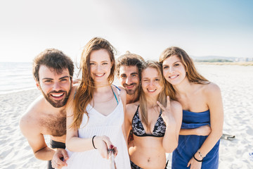 Selfie on the beach, summer day at sunset. Five friends in swimwear, two men and three women take photo near sea