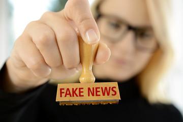 Frau mit Stempel FAKE NEWS