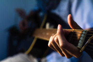 close up of hand playing guitar in high contrast tone