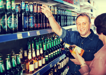 Portrait of an elderly couple buying a beer