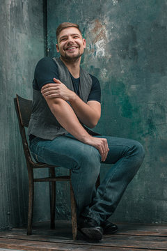 Portrait of smiling happy man sitting on the chair in studio