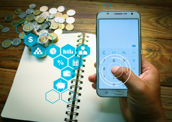 Hand holding a smart phone with finger on white touch screen. Rows of coins stack in banking and saving concept with money and finance icons.
