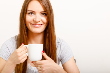 Smiling young woman holding cup of tea