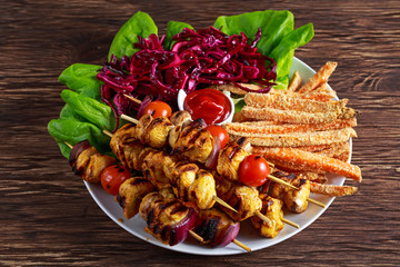 Chicken skewers marinated in turmeric yogurt served with sweet potato and vegetables