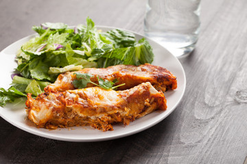 Spicy chicken enchiladas with a side of light green salad on a dark wood background horizontal shot