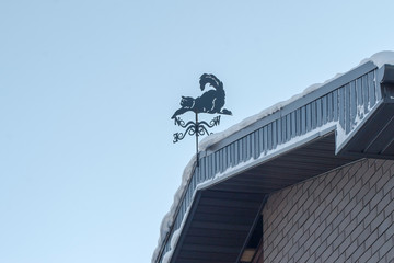 house covered with a thick layer of snow and weather vane on the