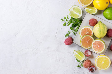 Variety of whole and sliced citrus fruits pink tiger lemon, lemon, lime, mint and exotic lichee on white square plate over white concrete textured background. Top view, copy space. Healthy eating