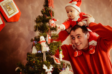 The father holds of hands his son near Christmas tree