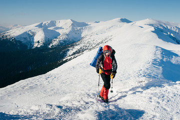 Man with backpack is hiking in snowy winter mountains