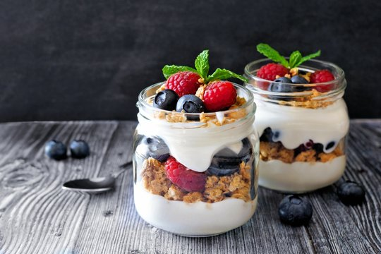Healthy blueberry and raspberry parfaits in mason jars, scene on dark rustic background