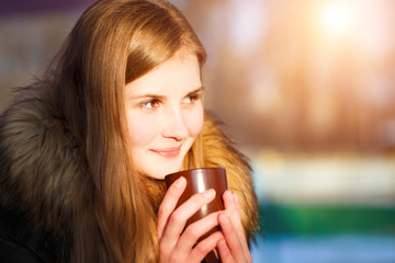 Young girl holding cup of coffee in winter park. Pretty caucasian woman with hot drink