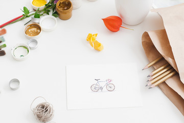 Pictured bicycle with drawing supplies. Artisan workplace with pencils set, gouache and picture of cute bike. Art, craft, creativity, inspiration of sport concept
