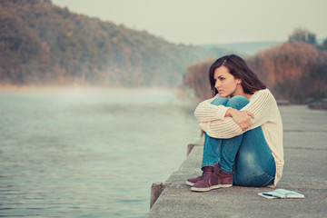 Lonely girl sitting by lake in the cold autumn morning.