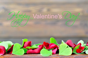 Happy Valentines Day card with red rose petals and heart shaped leaves