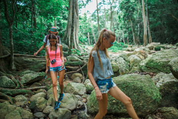 group of russian tourists walking through rocky stream in thai jungle