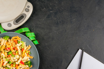 Concept of dieting, counting calories: a plate of healthy food (whole grain pasta with vegetables), scales for weighing food, tape measure, notepad and pencil for a food diary, top view, copy space