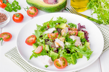 Fresh salad with chicken, avocado, tomatoes and flax seeds on a plate on white wooden background. Healthy food.