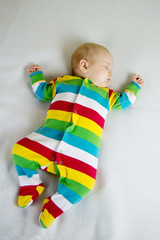 baby in striped suit lying on a light blanket