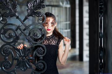 Mysterious woman in venetian carnival mask near wrought iron gate