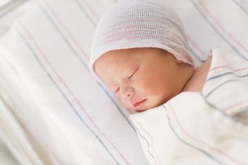 Newborn infant baby boy lying in a hospital bed