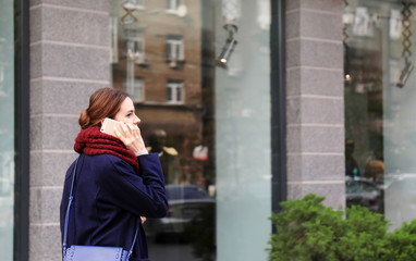 Young beautiful businesswoman talking on phone beside office building