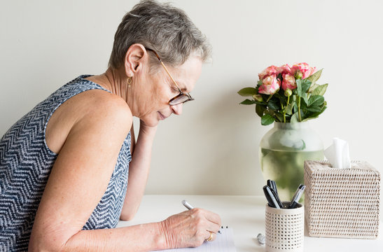 Profile view of older woman with short grey hair and glasses sitting at desk writing (selective focus)