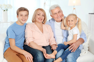 Cute happy children with grandparents sitting on sofa in living room
