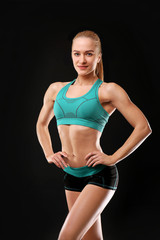 Young athletic woman on black background