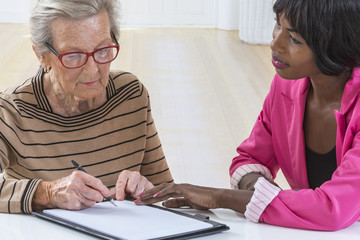 Senior woman signing contract with agent at home