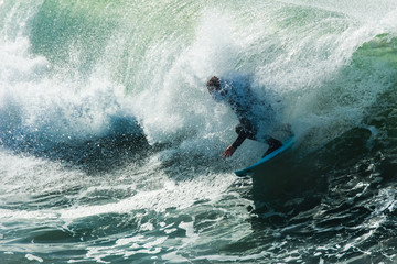 Surfer engulfed by a wave continues to ride through