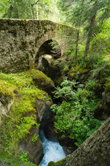 Ancient Roman stone bridge over a river gorge deep in a French forest