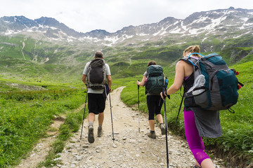 Three young hikers follow a dirt trail towards a large range of mountains in the French Alps