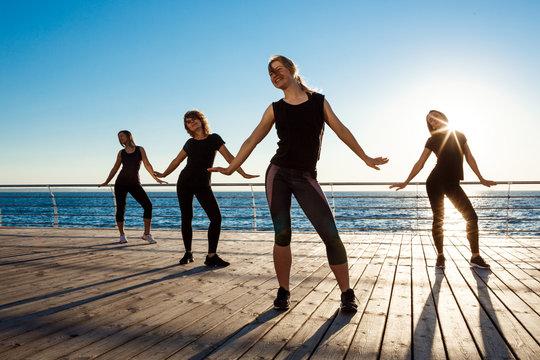 Silhouettes of sportive girls dancing zumba near sea at sunrise.