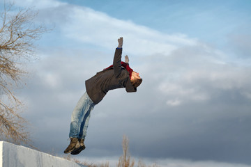 Man doing back flips. He is dressed in coat, scarf, jeans and gloves. Winter.