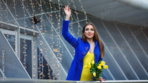 Young attractive girl in a blue coat and yellow dress holding a bouquet of  yellow tulips d6ae3c226