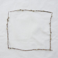 Square frame made from pussy willow branches on muslin fabric texture with copy space from top view